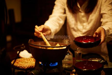 せんべい汁を取り分ける女性の写真素材 [FYI02055673]