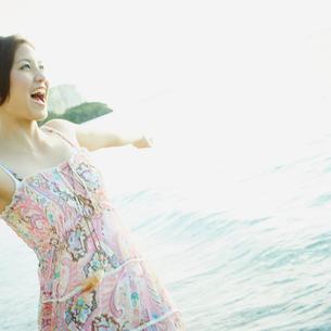 両腕を広げる女性と海の写真素材 [FYI02055696]