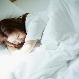 ベッドに横たわる女性の写真素材 [FYI02055708]