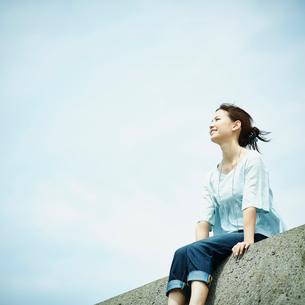 防波堤に座る女性と青空の写真素材 [FYI02055761]