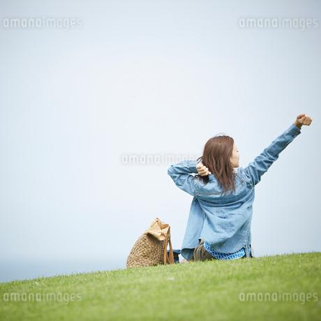 芝生の上で伸びをする女性の後ろ姿の写真素材 [FYI02055807]