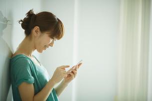スマートフォンを操作する女性の横顔の写真素材 [FYI02055893]