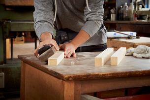 鉋で木材を削る男性の手元の写真素材 [FYI02055951]