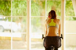 エアロバイクで運動する女性の後ろ姿の写真素材 [FYI02055966]