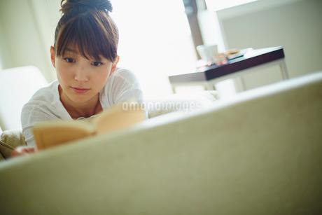ソファに寝転び本を読む女性の写真素材 [FYI02056029]