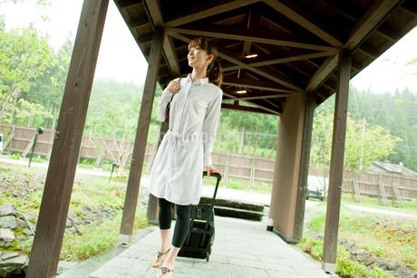 キャリーバッグを引いて歩く女性の写真素材 [FYI02056065]