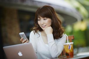 オープンカフェで仕事をする女性の写真素材 [FYI02056075]