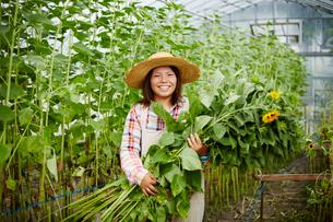 ヒマワリを持つ笑顔の農婦の写真素材 [FYI02056080]