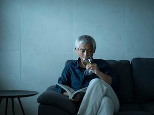 ワインを飲みながら本を読むシニア男性の写真素材 [FYI02056089]