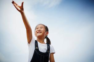 片手を上げる女の子の写真素材 [FYI02056101]