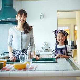 キッチンに立つ笑顔の女の子と母親の写真素材 [FYI02056106]