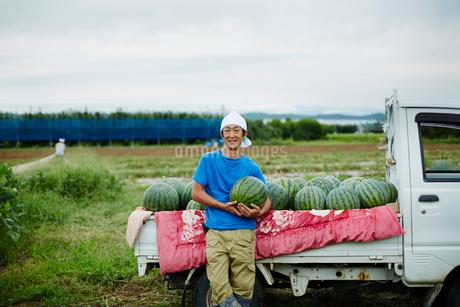 スイカを積んだトラックとスイカを抱える笑顔の農夫の写真素材 [FYI02056107]