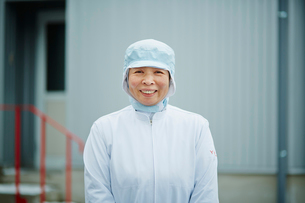 食品衛生服を着た笑顔のシニア女性の写真素材 [FYI02056129]