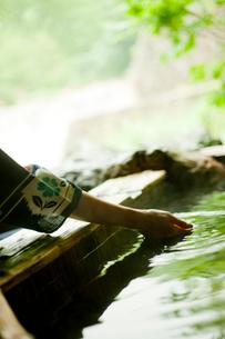 露天風呂の湯をすくう女性の手の写真素材 [FYI02056148]