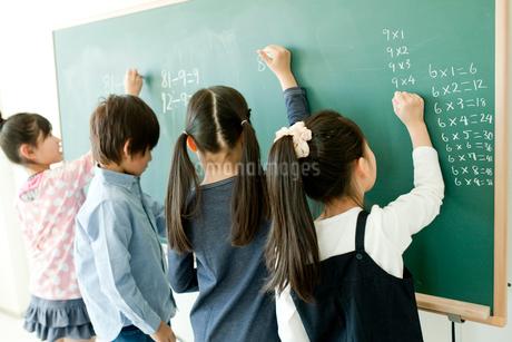 黒板で算数の問題を解く小学生4人の写真素材 [FYI02056150]