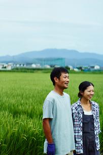 水田と笑顔の農家夫婦の写真素材 [FYI02056169]