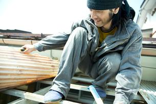 屋根の修繕をする男性の写真素材 [FYI02056189]