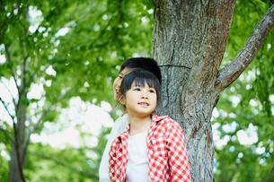 木の幹にもたれる笑顔の男の子と女の子の写真素材 [FYI02056208]