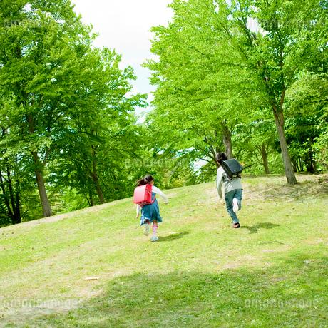 新緑の公園を走る小学生の男の子と女の子の写真素材 [FYI02056224]