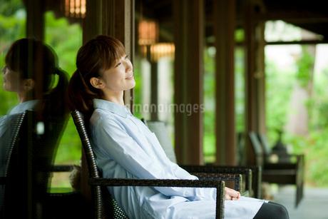 椅子に座りくつろぐ女性の写真素材 [FYI02056237]