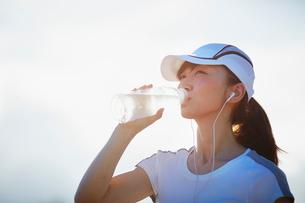 ペットボトルの水を飲むスポーツウェア姿の女性の写真素材 [FYI02056267]