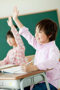 教室で挙手する小学生の男の子と女の子の写真素材 [FYI02056274]