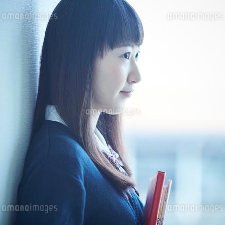 壁に寄りかかる女子学生の横顔の写真素材 [FYI02056324]