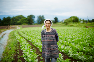 畑に立つ笑顔の農婦の写真素材 [FYI02056334]