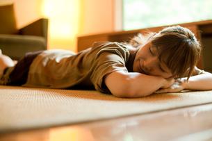 床に寝転ぶ女性の写真素材 [FYI02056362]