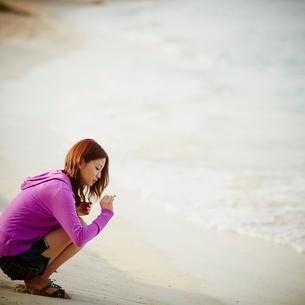 砂浜で拾ったサンゴの欠片を見つめる女性の写真素材 [FYI02056364]