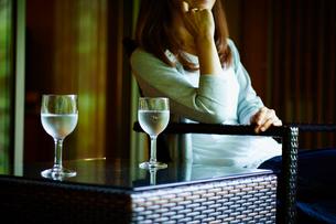 テーブルの上の水が入ったグラスと椅子に座る女性の写真素材 [FYI02056373]