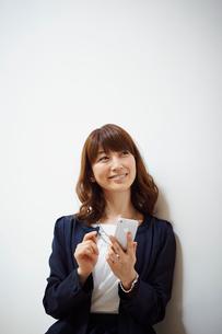 スマートフォンを操作するビジネス女性の写真素材 [FYI02056386]