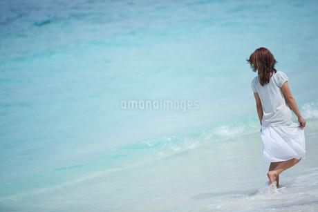 波打ち際を歩く女性の後姿の写真素材 [FYI02056391]