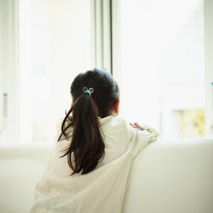ソファにもたれ外を見る女の子の後姿の写真素材 [FYI02056407]