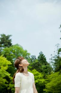 新緑と青空と上を向き目を閉じる女性の写真素材 [FYI02056420]