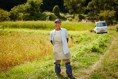 畑の前に立つ笑顔の農夫の写真素材 [FYI02056494]