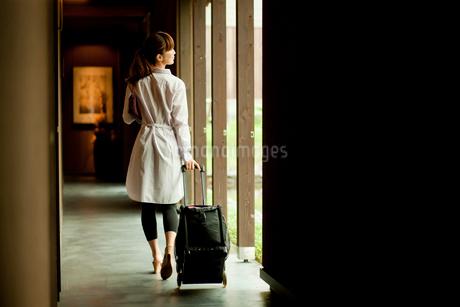 キャリーバッグを引いて歩く女性の後ろ姿の写真素材 [FYI02056498]
