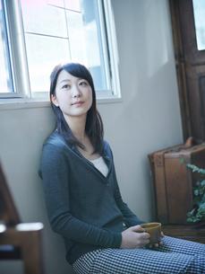 コーヒーカップを持ってくつろぐ女性の写真素材 [FYI02056548]