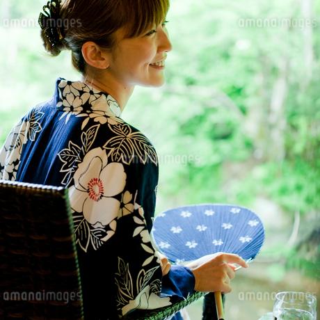 団扇を持ち椅子に座る浴衣姿の女性の写真素材 [FYI02056549]