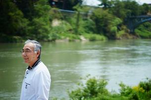 川を眺める笑顔のシニア男性の写真素材 [FYI02056552]