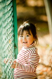 フェンスと笑顔の女の子の写真素材 [FYI02056593]