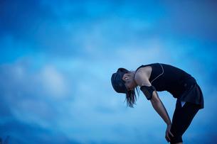 休憩するランニングウェア姿のミドル女性の写真素材 [FYI02056655]