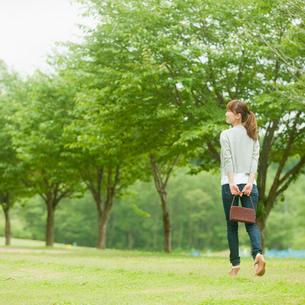 新緑の並木と歩く女性の写真素材 [FYI02056671]