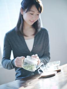 ハーブティーをカップに注ぐ女性の写真素材 [FYI02056672]