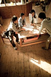 作業場で打ち合わせをする4人の若者達の写真素材 [FYI02056687]