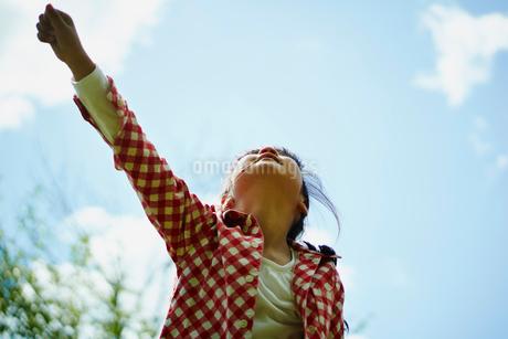 片手を上げる女の子と青空の写真素材 [FYI02056693]
