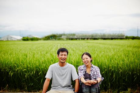 水田と笑顔の農家夫婦の写真素材 [FYI02056709]