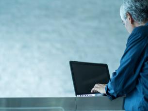 ノートパソコンを操作するシニア男性の写真素材 [FYI02056760]
