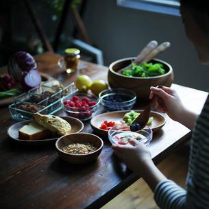 フルーツグラノーラヨーグルトを食べる女性の手元の写真素材 [FYI02056810]