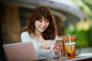 オープンカフェで仕事をする女性の写真素材 [FYI02056817]